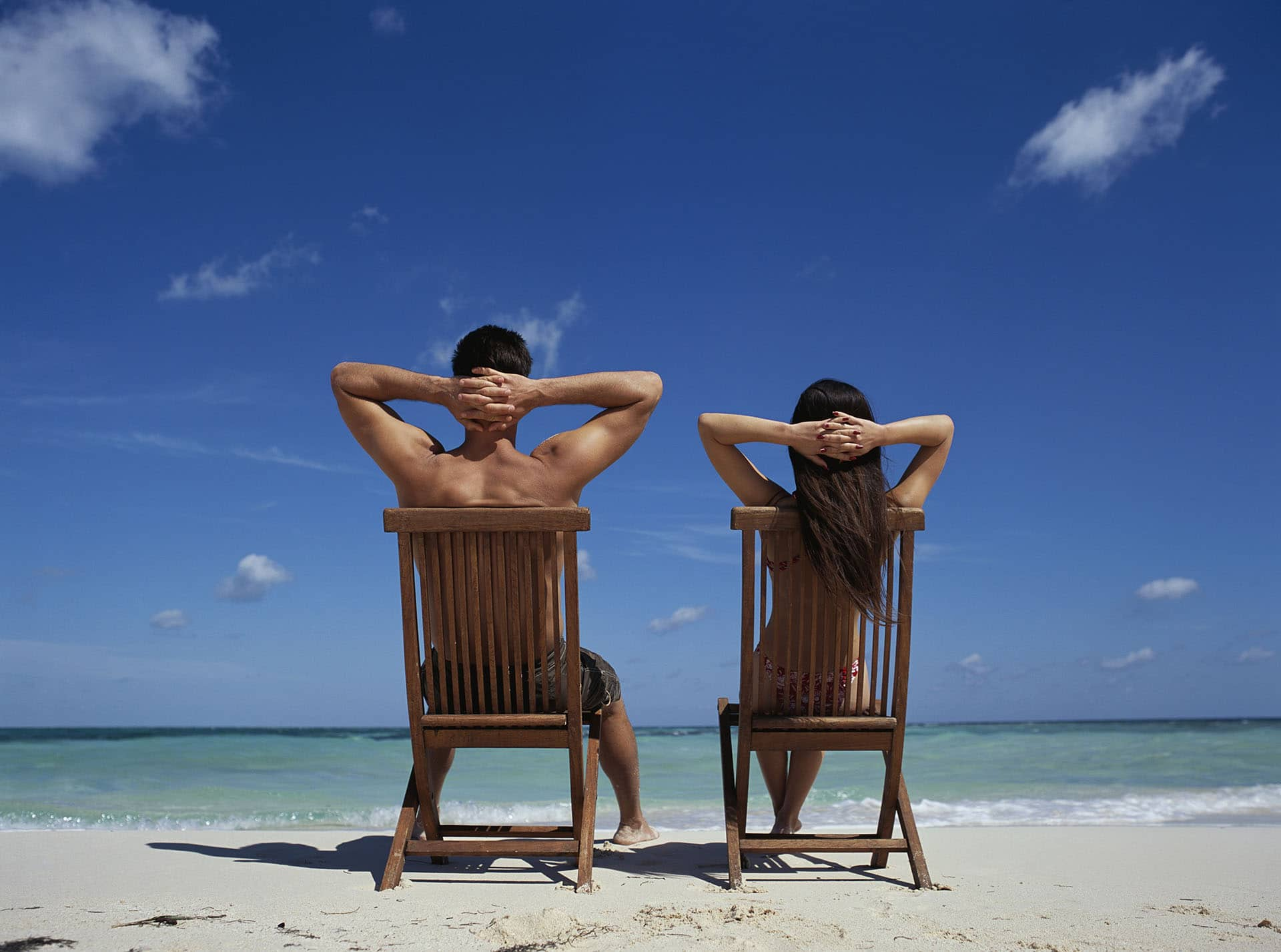 Couple Relaxing in Lounge Chairs at Beach --- Image by © Franco Vogt/CORBIS